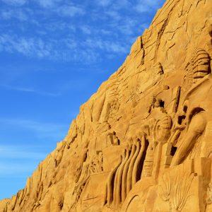 50/50 sand og hav - sand skulptur med blå himmel